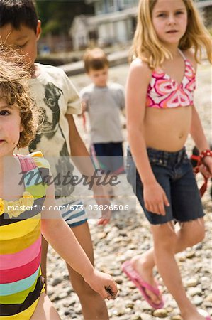 group of children walking on beach Stock Photo - Premium Royalty-Free, Image code: 673-03826506