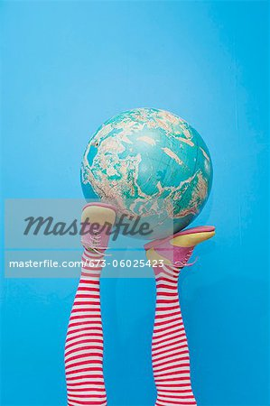 Legs in striped socks with colorful shoes holding globe Stock Photo - Premium Royalty-Free, Image code: 673-06025423