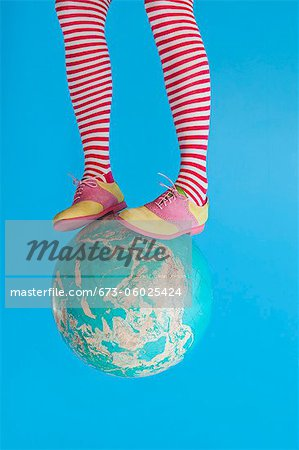 Legs in striped socks with colorful shoes on globe Stock Photo - Premium Royalty-Free, Image code: 673-06025424