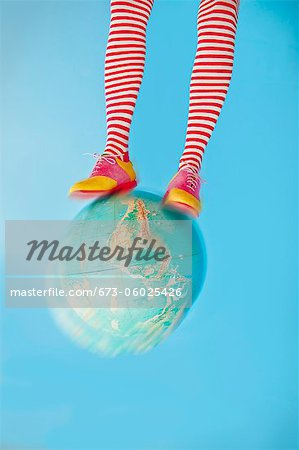 Legs in striped socks with colorful shoes on globe Stock Photo - Premium Royalty-Free, Image code: 673-06025426