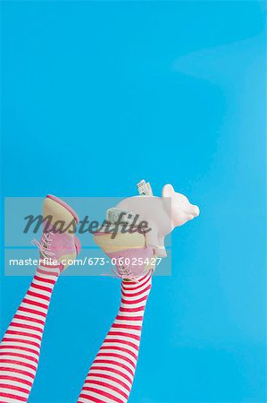 Legs in striped socks with colorful shoes holding piggy bank Stock Photo - Premium Royalty-Free, Image code: 673-06025427