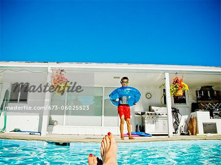 Boy in floaty standing next to pool Stock Photo - Premium Royalty-Free, Image code: 673-06025523