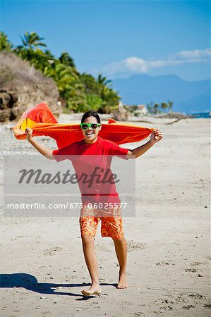 Teen girl running on beach with towel cape Stock Photo - Premium Royalty-Free, Image code: 673-06025577