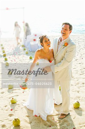 Bridal couple laughing on beach Stock Photo - Premium Royalty-Free, Image code: 673-06025623