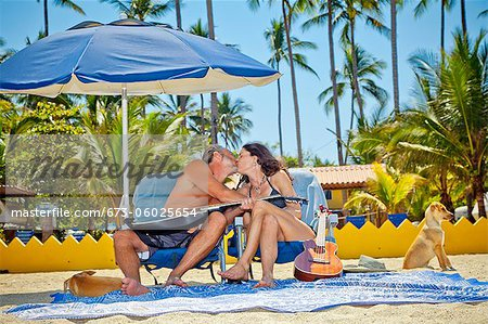 Man and woman kissing while seated in beach chairs Stock Photo - Premium Royalty-Free, Image code: 673-06025654
