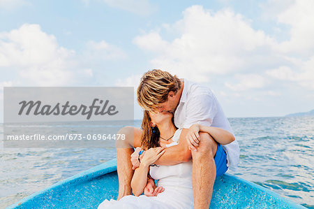 Man and woman embracing in bow of boat Stock Photo - Premium Royalty-Free, Image code: 673-06964478