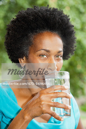 Woman drinking glass of water Stock Photo - Premium Royalty-Free, Image code: 673-06964561
