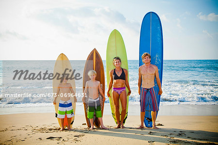Family standing on beach with surfboards Stock Photo - Premium Royalty-Free, Image code: 673-06964631