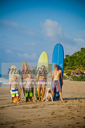 Family standing on beach with surfboards Stock Photo - Premium Royalty-Free, Image code: 673-06964632