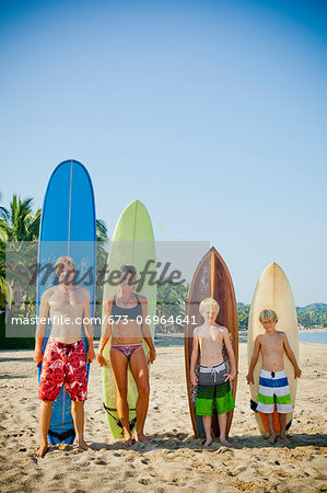 Family of four standing in front of surfboards Stock Photo - Premium Royalty-Free, Image code: 673-06964641