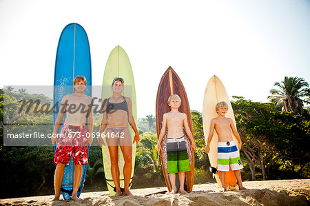 Family of four standing in front of surfboards Stock Photo - Premium Royalty-Free, Image code: 673-06964642