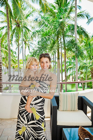 Stylish woman with baby near palm trees Stock Photo - Premium Royalty-Free, Image code: 673-06964644