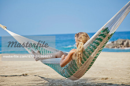 Young woman in hammock on beach Stock Photo - Premium Royalty-Free, Image code: 673-06964657