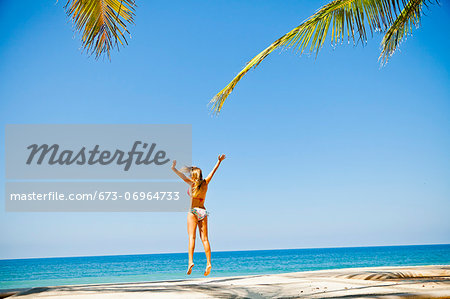 Woman in bikini jumping on beach Stock Photo - Premium Royalty-Free, Image code: 673-06964733