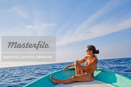 Woman sitting in bow of boat Stock Photo - Premium Royalty-Free, Image code: 673-06964764
