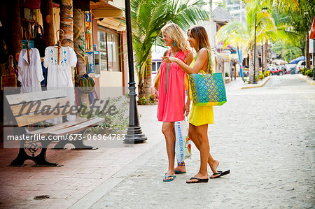 Two women shopping in seaside town Stock Photo - Premium Royalty-Free, Image code: 673-06964783