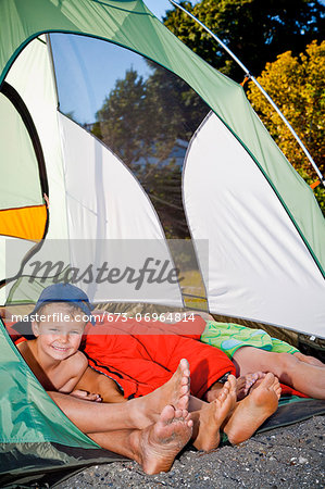 Young boy's face and pairs of feet poking out of tent Stock Photo - Premium Royalty-Free, Image code: 673-06964814