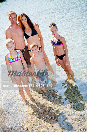 Family standing in shallow water Stock Photo - Premium Royalty-Free, Image code: 673-06964840