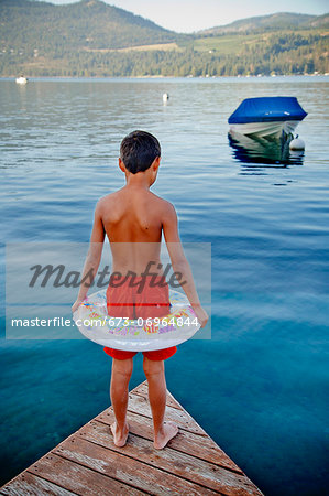 Young boy wearing float ring on dock Stock Photo - Premium Royalty-Free, Image code: 673-06964844