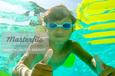Underwater view of a boy swimming wearing goggles Stock Photo - Premium Royalty-Free, Image code: 673-08139177