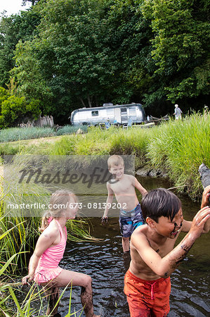 Children playing in a muddy creek Stock Photo - Premium Royalty-Free, Image code: 673-08139202
