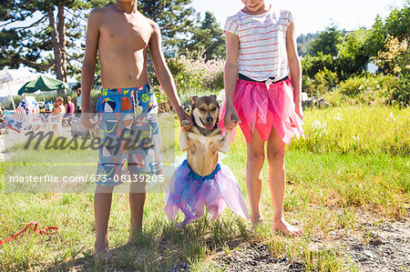 Small dog in a tutu with his paws held up by children Stock Photo - Premium Royalty-Free, Image code: 673-08139205