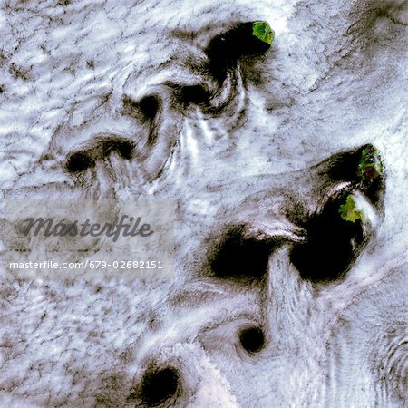 Von Karman vortices. Coloured composite satellite image of clouds forming von Karman vortices, an effect that occurs when an object disturbs the flow of a fluid, leading to the creation of a chain of spiral eddies (a vortex street). In this case, the objects causing vortex streets to form are islands in the Kuril Islands chain between Russia and Japan. The effect occurs at all scales and it is imp