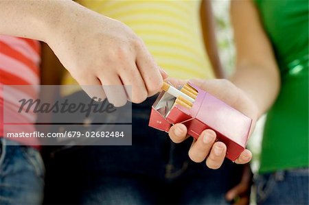 Underage smoking. Young teenage girl taking a cigarette from her friend's packet. Stock Photo - Premium Royalty-Free, Image code: 679-02682484