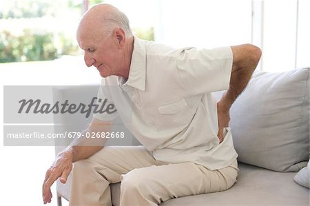 Lower back pain. Man rubbing his aching back. Stock Photo - Premium Royalty-Free, Image code: 679-02682668