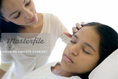 Hospital visit. Mother stroking her daughter's hair as she sleeps in a hospital bed. Stock Photo - Premium Royalty-Free, Image code: 679-02682801