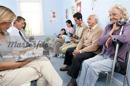 General practice waiting room  filled with patients. Stock Photo - Premium Royalty-Free, Image code: 679-02685707