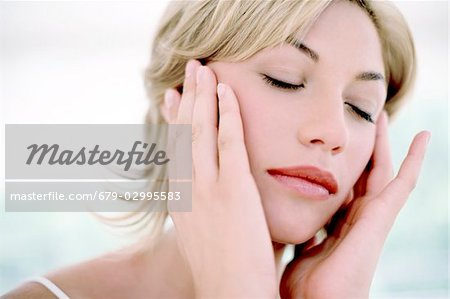 Woman touching her face Stock Photo - Premium Royalty-Free, Image code: 679-02995583