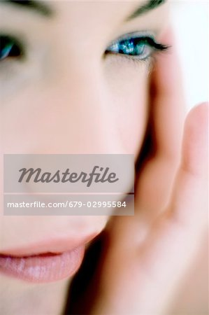 Woman touching her face Stock Photo - Premium Royalty-Free, Image code: 679-02995584