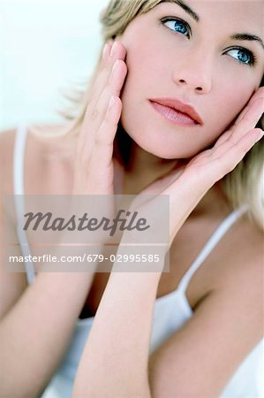 Woman touching her face Stock Photo - Premium Royalty-Free, Image code: 679-02995585