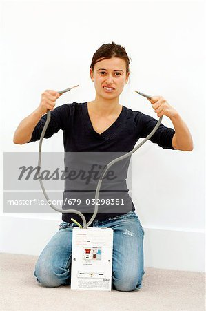 Woman joking while doing DIY. She is holding the cables to a high-voltage mains box, threatening to touch the ends together. Stock Photo - Premium Royalty-Free, Image code: 679-03298381