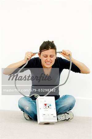 Woman joking while doing DIY. She is holding the cables to a high-voltage mains box to her head. Stock Photo - Premium Royalty-Free, Image code: 679-03298382