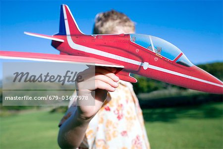 Boy playing with a model aeroplane. Stock Photo - Premium Royalty-Free, Image code: 679-03677978