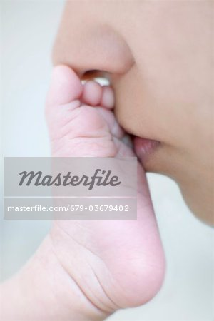 Mother kissing her newborn's foot. Stock Photo - Premium Royalty-Free, Image code: 679-03679402