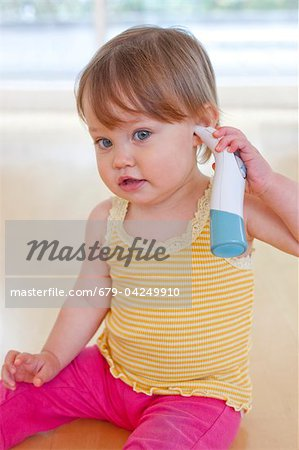 Toddler playing with thermometer Stock Photo - Premium Royalty-Free, Image code: 679-04249910