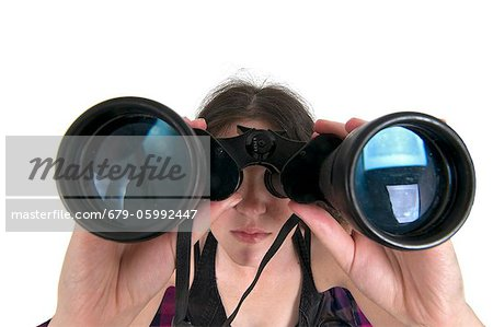 Woman looks through a binoculars facing camera wide angle view Stock Photo - Premium Royalty-Free, Image code: 679-05992447