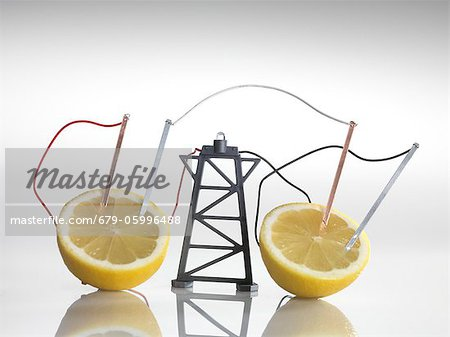 Electrical circuit with lemons. A chemical reaction between the copper and zinc plates and the lemon produces a small current, that is able to power a light bulb. Stock Photo - Premium Royalty-Free, Image code: 679-05996488