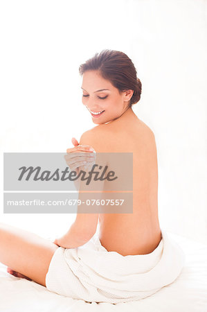 Woman applying body lotion. Stock Photo - Premium Royalty-Free, Image code: 679-07607557