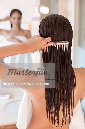 Woman brushing her hair. Stock Photo - Premium Royalty-Free, Image code: 679-07607561