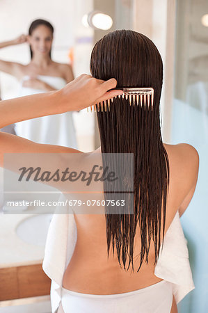 Woman brushing her hair. Stock Photo - Premium Royalty-Free, Image code: 679-07607563