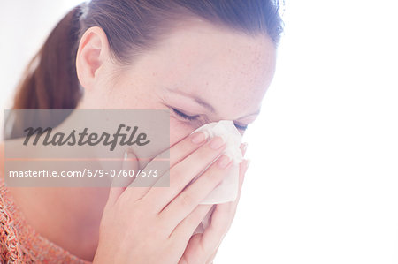 Young woman sneezing. Stock Photo - Premium Royalty-Free, Image code: 679-07607573