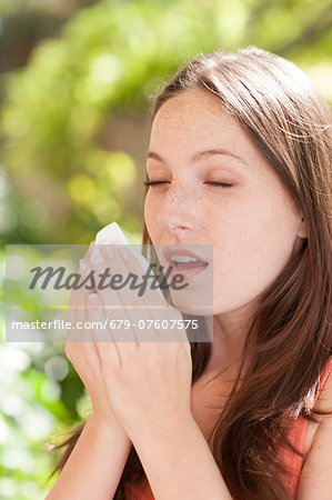 Young woman sneezing. Stock Photo - Premium Royalty-Free, Image code: 679-07607575