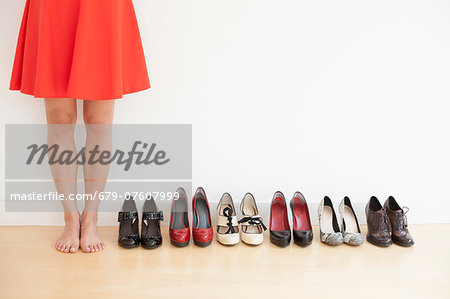 Woman standing next to a row of shoes. Stock Photo - Premium Royalty-Free, Image code: 679-07607999