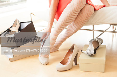 Woman trying on a pair of new shoes. Stock Photo - Premium Royalty-Free, Image code: 679-07608000