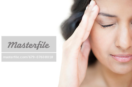 Portrait of a woman touching her head with her eyes closed. Stock Photo - Premium Royalty-Free, Image code: 679-07608018