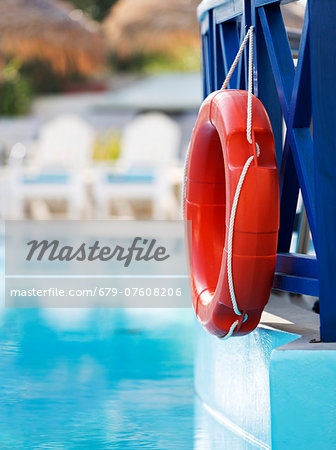 Life ring hanging on the railings of a hotel swimming pool. Stock Photo - Premium Royalty-Free, Image code: 679-07608206